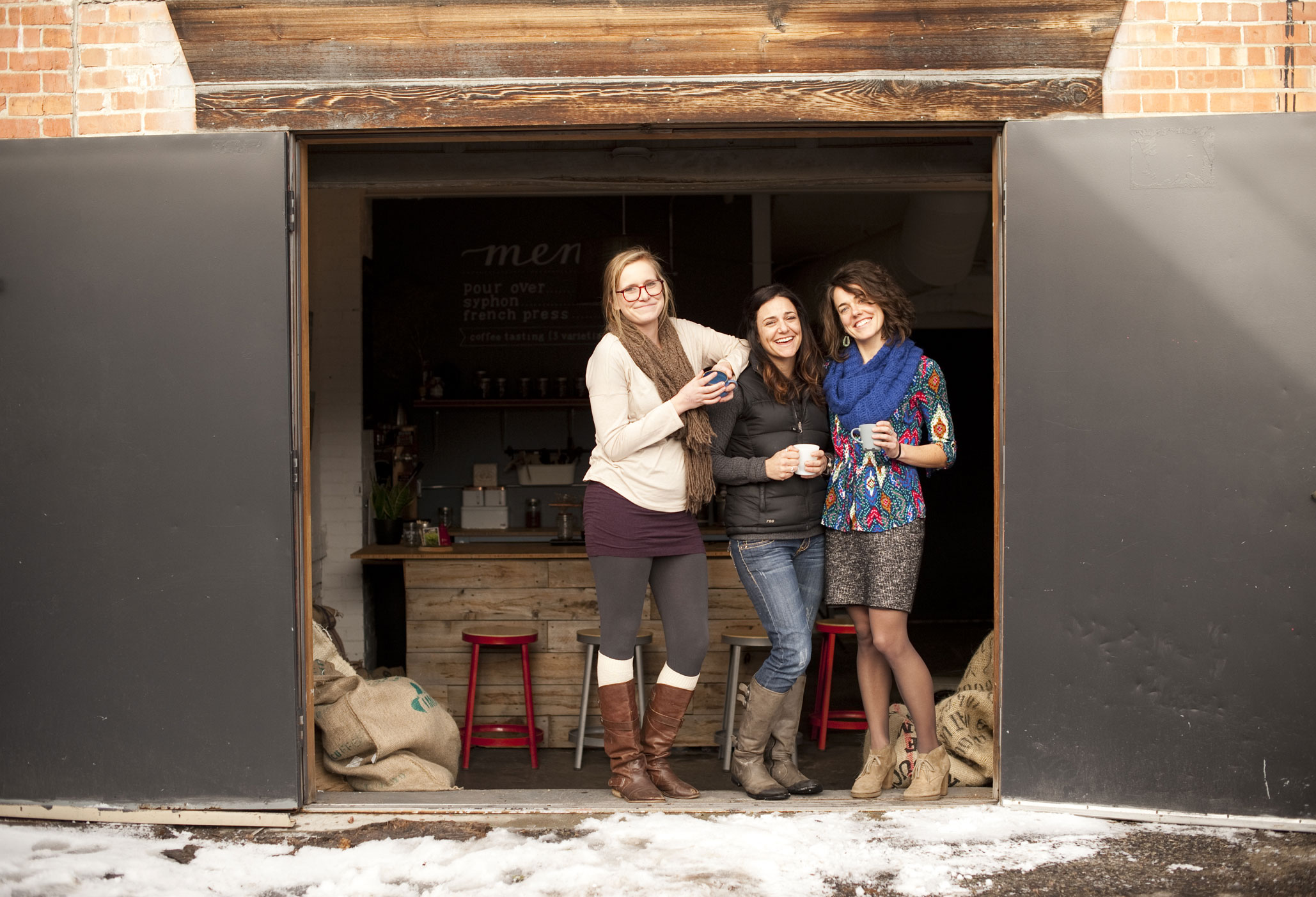 Little Red Wagon Coffee Roasters owners Natalie Van Dusen (center) and Kelly Meredith (right) pictured in their alley entrance with LRWCR's marketing guru Deejay Newell